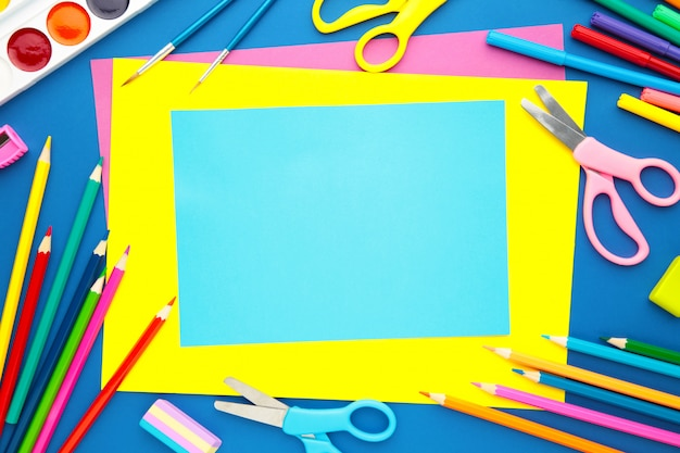 Popiera szkoły pojęcie na błękitnym tle z kopii przestrzenią. widok z góry
