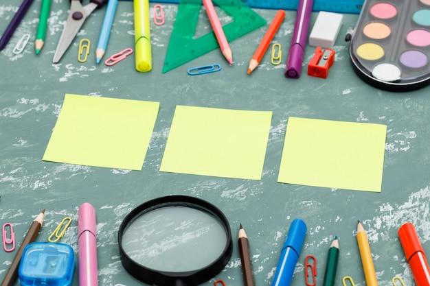 Popiera szkoły pojęcie z kleistymi notatkami, powiększający - szkło, szkolne dostawy na tynku tła wysokiego kąta widoku.