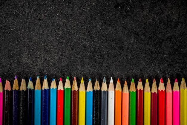 Popiera szkoły pojęcie z książka budzika koloru ołówków chalkboard tłem