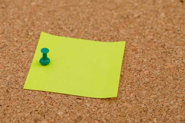 Popiera szkoły pojęcie z przypiętą kleistą notatką na korek deski wysokiego kąta widoku.