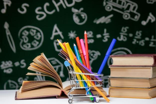 Popiera szkoły tło z książkami, ołówkami i kulą ziemską na bielu stole na zielonym blackboard tle.
