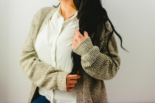 Popiersie brunetki kobieta trzyma jej długie włosy z jej rękami.
