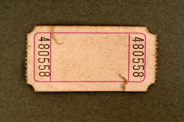 Poplamiony i uszkodzony pusty bilet wstępu na cętkowanym tle brązowego papieru.