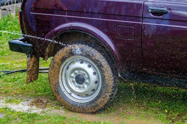 Popołudniowa myjnia samochodowa na świeżym powietrzu ze strumieniem wody z węża ogrodowego