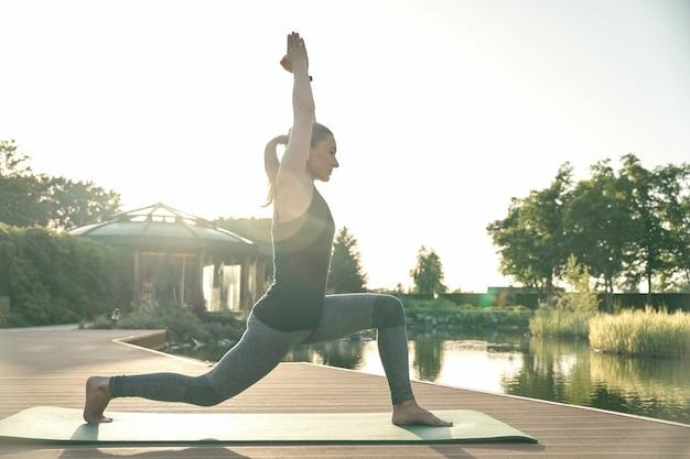 Popraw sobie ujęcie pełnej długości zrelaksowanej kobiety stojącej w pozie jogi podczas wykonywania jogi na macie