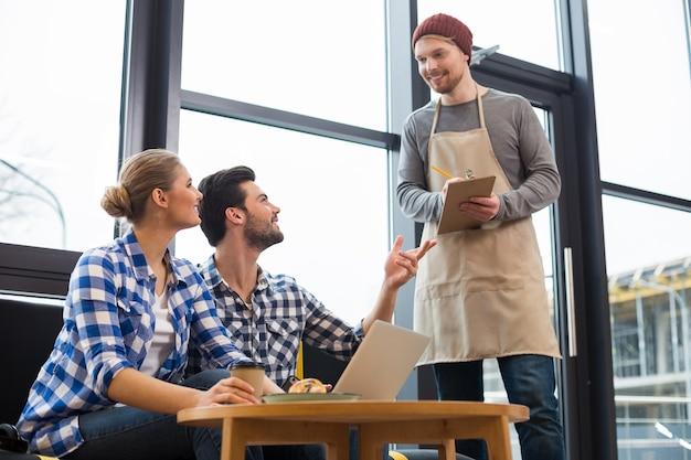 Poproszę dwie filiżanki. pozytywni radośni młodzi ludzie siedzący razem i patrząc na kelnera zamawiając kawę