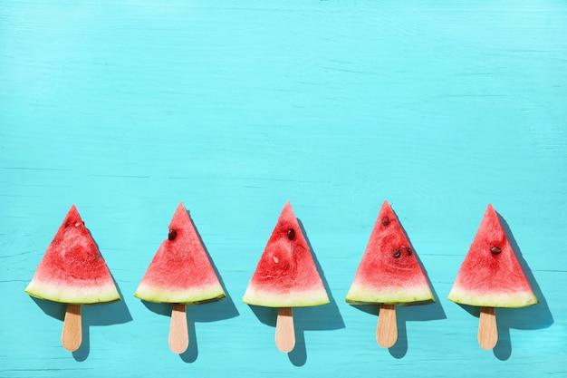 Popsicles kawałek arbuza na drewnianym niebieskim tle.