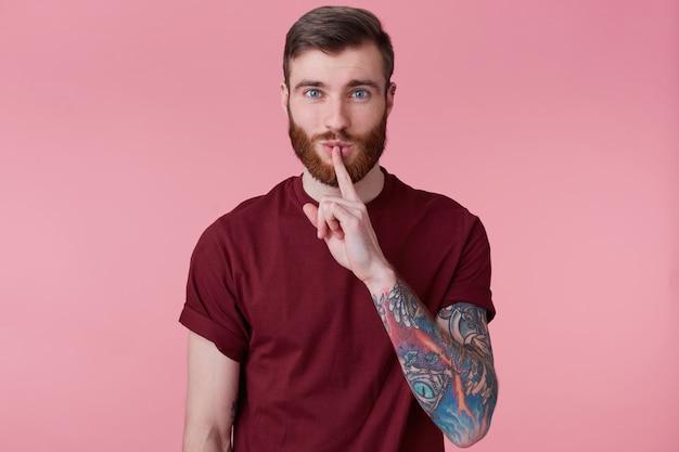 Poptrait młodego brodatego mężczyzny z wytatuowaną ręką odizolowaną na różowym tle, z szeroko otwartymi oczami, trzyma palec wskazujący na ustach, milczy, nie hałasuje, demonstruje gest ciszy.