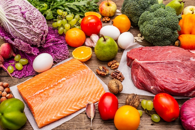 Popularna dieta paleo / pegan. koncepcja zdrowej żywności zrównoważonej. zestaw świeżych produktów, surowego mięsa, łososia, warzyw i owoców