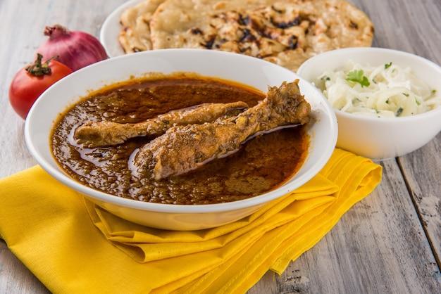 Popularne czerwonawe curry z kurczaka lub masala, z wyraźnym kawałkiem nogi, podawane w misce z ryżem pilau, chapati lub roti i sałatką
