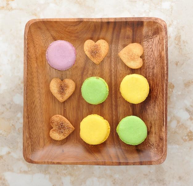 Popularne francuskie deserowe macarons i ciasto w kształcie serca na drewnianym talerzu