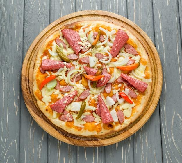 Popularne polewy do pizzy w amerykańskich pizzeriach na drewnianej powierzchni