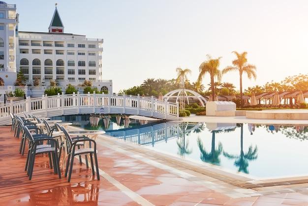 Popularny kurort amara dolce vita luxury hotel. z basenami i parkami wodnymi oraz terenem rekreacyjnym wzdłuż wybrzeża morskiego w turcji o zachodzie słońca. tekirova-kemer.