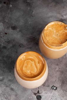 Popularny napój koreańska kawa dargon z kawy rozpuszczalnej, cukru, gorącej wody i mleka w szkle na szarym tle