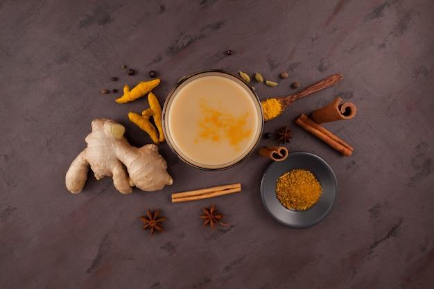 Popularny tradycyjny indyjski, azjatycki napój masala chai lub pikantna herbata ziołowa ze wszystkimi składnikami na brązowo
