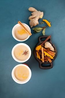 Popularny tradycyjny indyjski, azjatycki napój masala chai lub pikantna herbata ziołowa ze wszystkimi składnikami na niebiesko