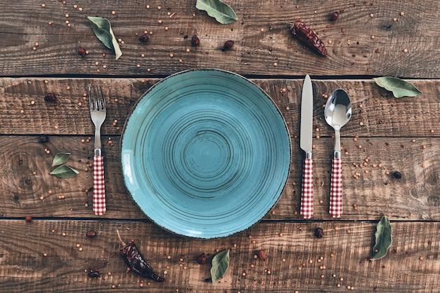 Pora obiadu. ujęcie pod dużym kątem pustego talerza, widelca, łyżki, noża