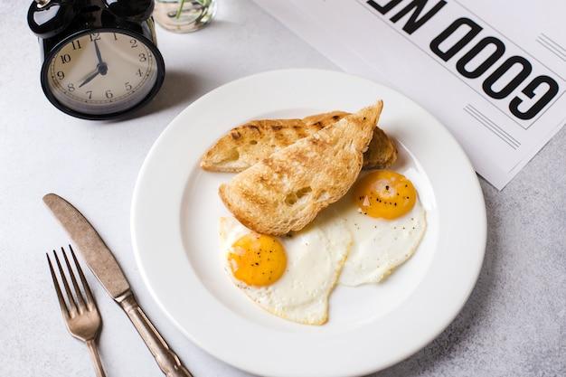 Pora śniadaniowa. dwa jajka sadzone z grzanką na śniadanie na jasnoszarym tle z gazetą i budzikiem
