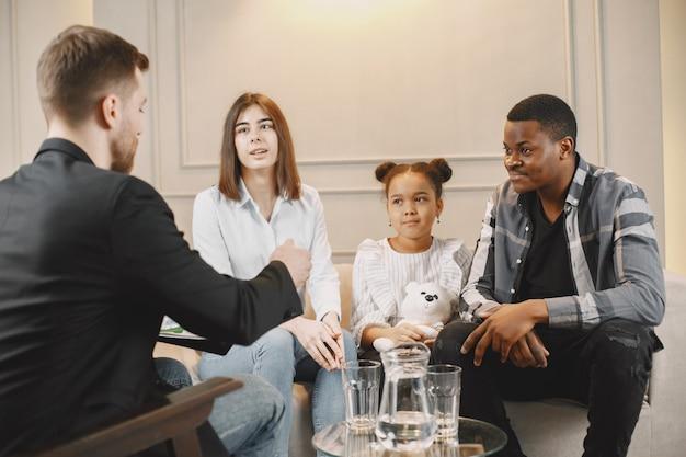Poradnia rodzinna w domu z terapeutą. psycholog pokazujący dziewczynce zdjęcia emocji, ojciec pochodzenia afrykańskiego amerykanina i europejska matka.