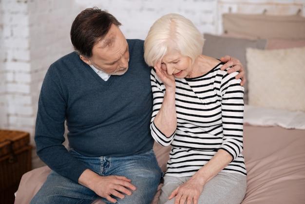 Poradzisz sobie. starszy mężczyzna wspiera swoją płaczącą żonę siedząc na łóżku w domu.