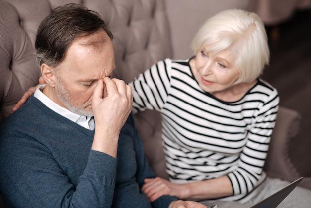Poradzisz sobie z tym. zamknij widok z góry na starszego mężczyznę dotykającego jego grzbietu nosa, mając silny ból głowy w pobliżu wspierającej żony.