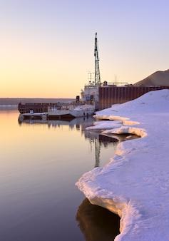 Poranek na brzegu ob zaśnieżony brzeg lodu na rzece wiosną molo portowe