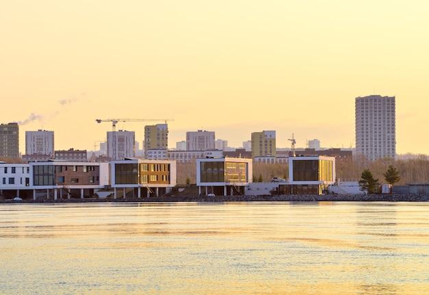 Poranek nad rzeką ob w nowosybirsku nowe niskie i wysokie budynki mieszkalne