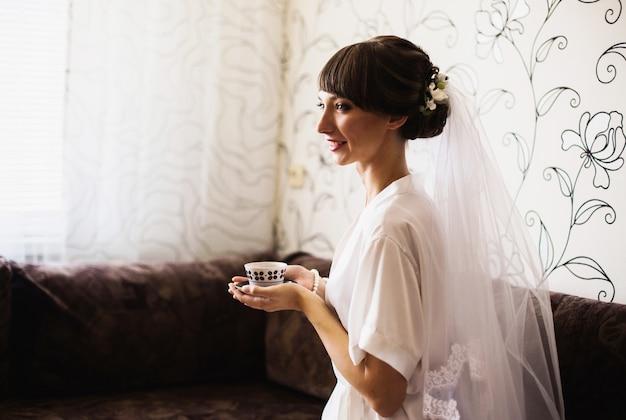 Poranek panny młodej. dziewczyna pije kawę z białej filiżanki. ślub