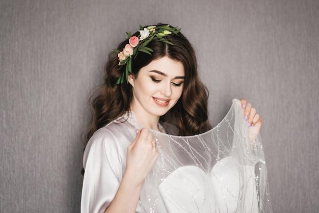 Poranek panny młodej. piękny portret panny młodej w peniuarem z lokami i świeżymi kwiatami w pobliżu sukni ślubnej.