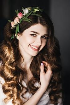Poranek panny młodej. piękny portret panny młodej w peniuarem z lokami i świeżymi kwiatami