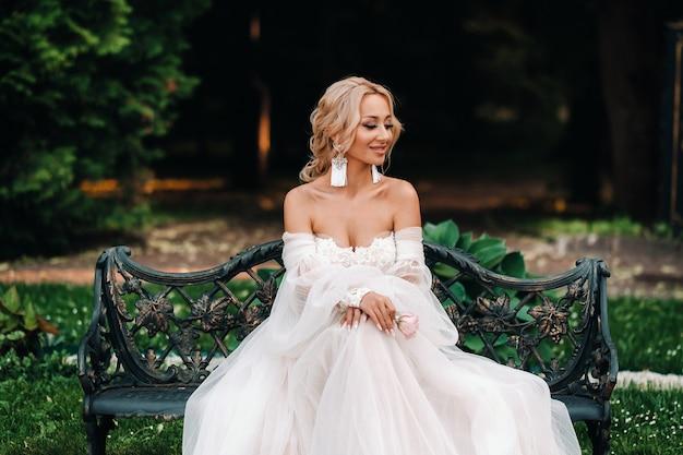 Poranek panny młodej w ogrodzie. portret młodej narzeczonej patrząc na jej suknię ślubną, wiszące na drzewie w ogrodzie.