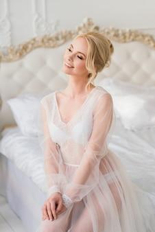 Poranek pięknej młodej narzeczonej w buduarowej sukience.