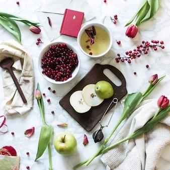 Poranek z herbatą i czerwonymi tulipanami na marmurowej makiecie