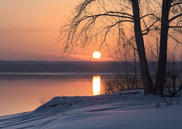 Poranek zimowy wschód słońca nad rzeką brzeg rzeki ob pokrywają niebieskie zaspy śnieżne