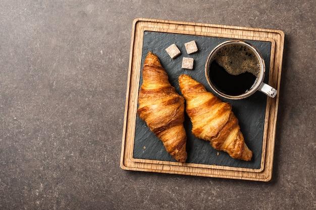 Poranna czarna kawa z rogalikami na desce do serwowania