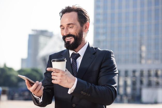 Poranna energia. wesoły biznesmen uśmiechający się przy użyciu swojego smartfona podczas picia kawy