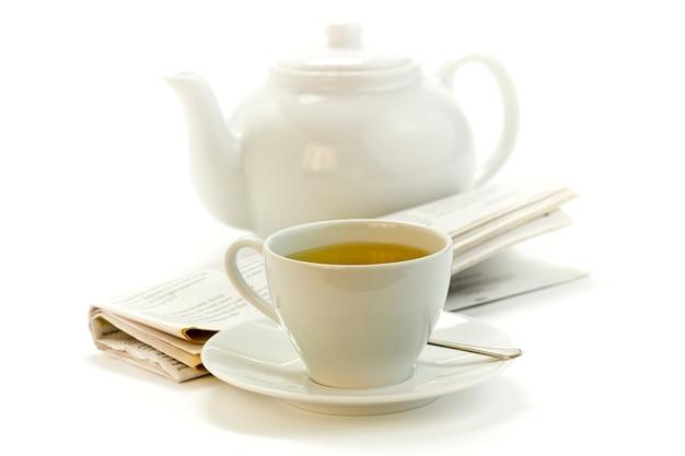 Poranna filiżanka herbaty, czajniczek i naciśnij na biały