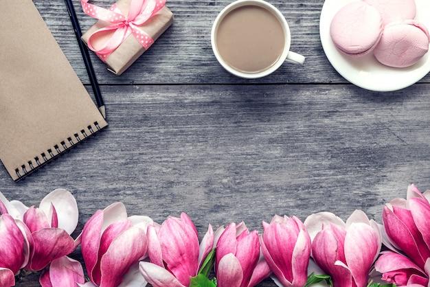 Poranna filiżanka kawy z mlekiem, ciastem macaron, pudełkiem prezentowym lub prezentowym i kwiatami magnolii na rustykalnym drewnianym stole. leżał płasko