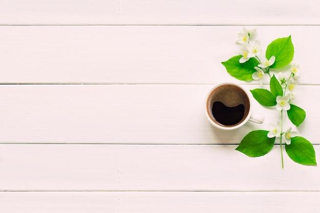 Poranna filiżanka świeżej kawy z wiosennych kwiatów na białym stole. widok z góry z miejscem na kopię.