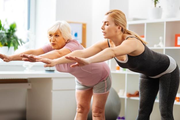 Poranna gimnastyka. ładna sprawna kobieta pochylająca się do przodu podczas treningu z pacjentem