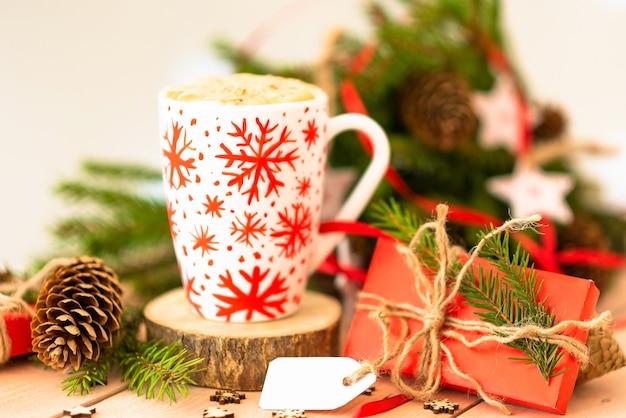 Poranna gorąca czekolada na boże narodzenie w białej filiżance z płatkami śniegu.