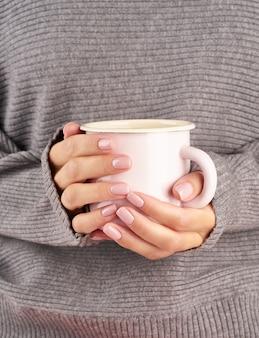 Poranna gorąca kawa w pracy w zimny jesienny poranek, ręce trzyma kubek z napojem, szary sweter