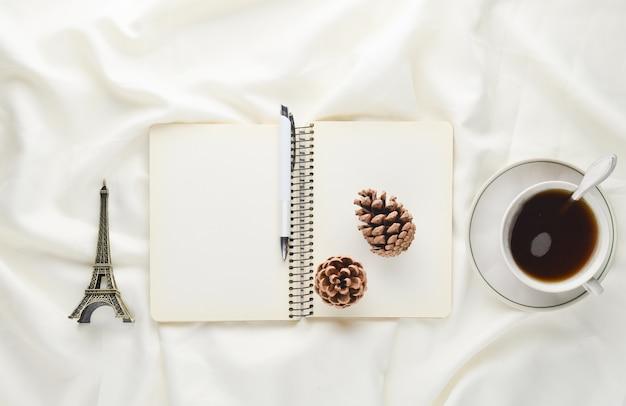 Poranna inspiracja, filiżanka herbaty, notatnik z długopisem, szyszka, pamiątka na białej prześcieradle. śniadanie na łóżku. pojęcie snów i chęć podróżowania. widok z góry.