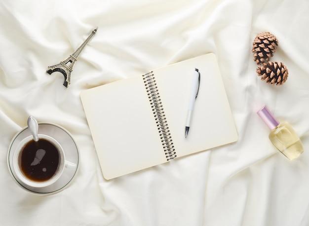 Poranna inspiracja i chęć wyjazdu do paryża. filiżanka herbaty, notatnik z długopisem, szyszka, pamiątka, perfumy na białej prześcieradle. śniadanie na łóżku. widok z góry.