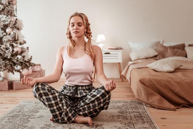 Poranna joga. medytacyjna spokojna dziewczyna siedzi na podłodze w pozie lotosu i jest głęboko w swoim umyśle