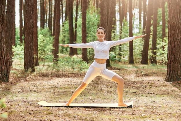 Poranna joga na świeżym powietrzu w parku, młoda piękna kobieta instruktorka ubrana w białą stylową odzież sportową stojącą na macie otaczającej drzewa, sport na świeżym powietrzu.