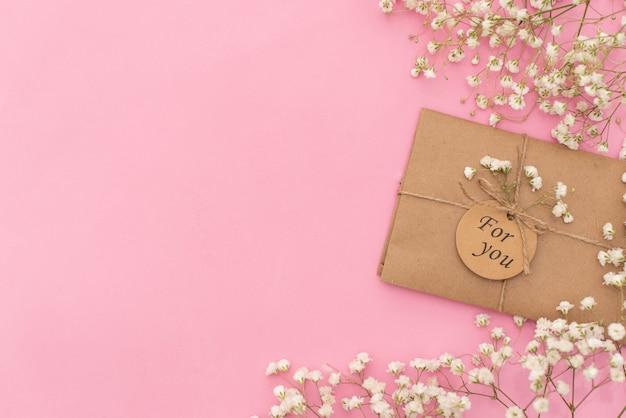 Poranna kawa, ciasto macaron, prezent lub pudełko prezentowe i kwiatek na lekkim stole z góry.
