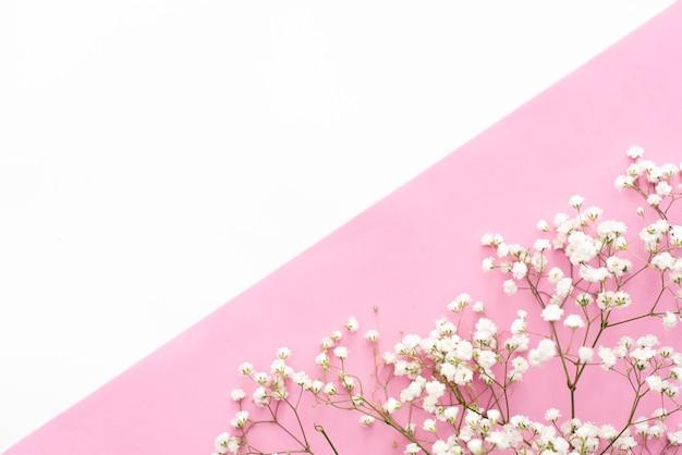 Poranna kawa, ciasto macaron, pudełko na prezent lub prezent i kwiat na różowym stole