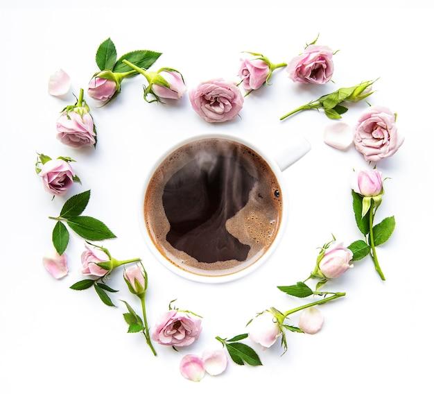Poranna kawa i piękne kwiaty róży na białym tle, widok z góry. przytulne śniadanie. leżał na płasko