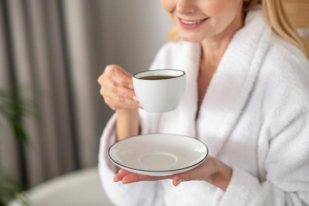 Poranna kawa. kobieta w białej szacie ma jej poranną kawę i wygląda na zadowoloną